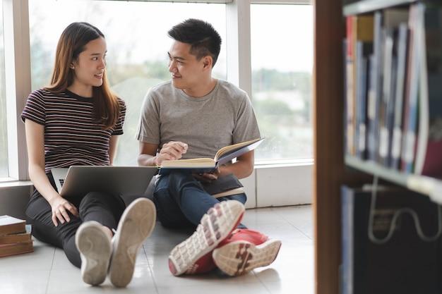 Zwei asiatische studenten, die nach projekt in der bibliothek suchen.