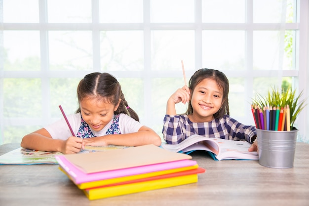 Zwei asiatische studentenmädchen genießen, buch tagsüber zu hause zu schreiben und zu lernen