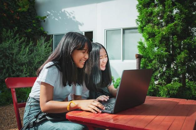 Zwei asiatische teenager tippen auf computer labtop glück emotion
