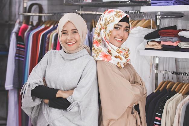 Zwei asiatische weibliche boutique-modegeschäftsinhaber