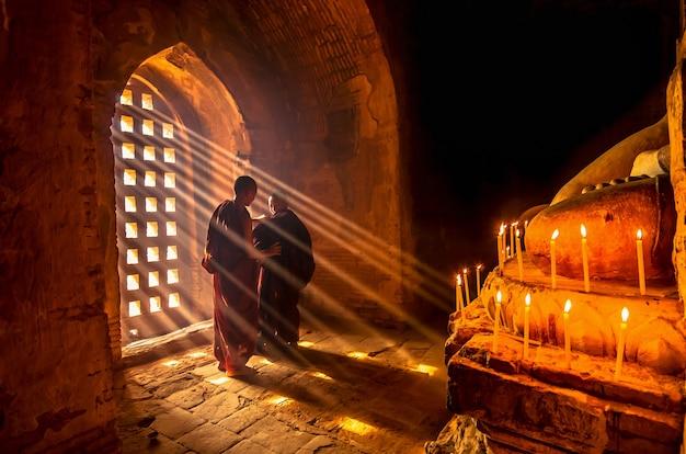 Zwei asiatischer burmish-mönch ändern die robe mit sonnenstrahl in der pagode bei bagan