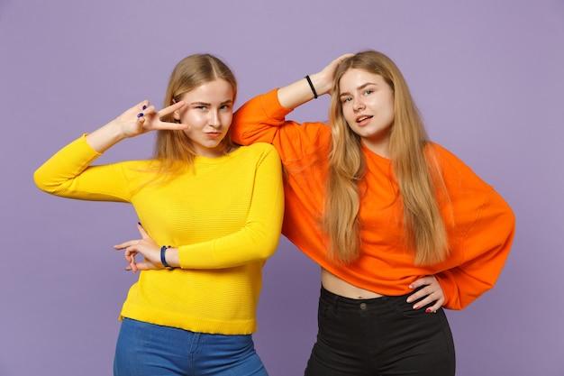 Zwei atemberaubende junge blonde zwillingsschwestern mädchen in bunten kleidern , die victory - zeichen einzeln auf pastellvioletter blauer wand zeigen . menschen-familien-lifestyle-konzept.
