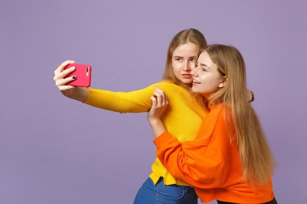 Zwei atemberaubende junge blonde zwillingsschwestern mädchen in bunten kleidern machen selfie-aufnahmen auf dem handy einzeln auf pastellvioletter blauer wand. menschen-familien-lifestyle-konzept.