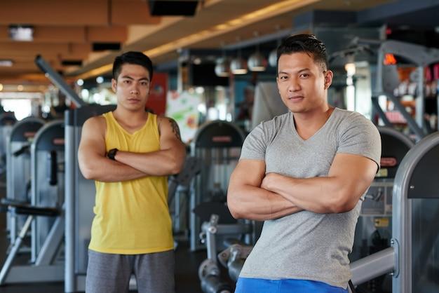 Zwei athletische asiatische männer mit den gekreuzten armen, die in der turnhalle aufwerfen