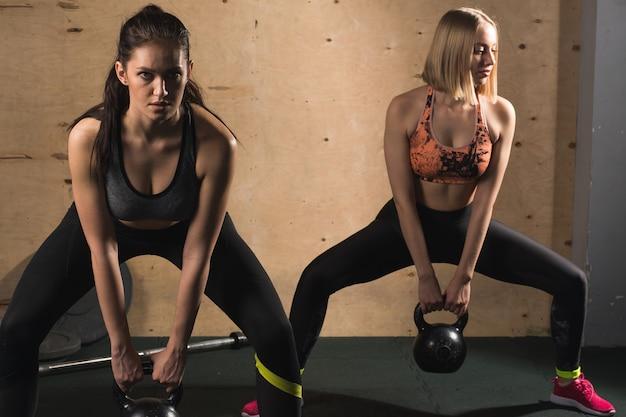 Zwei athletische frauen, die mit kesselglocke trainieren, während sie in der kniebeugeposition sind