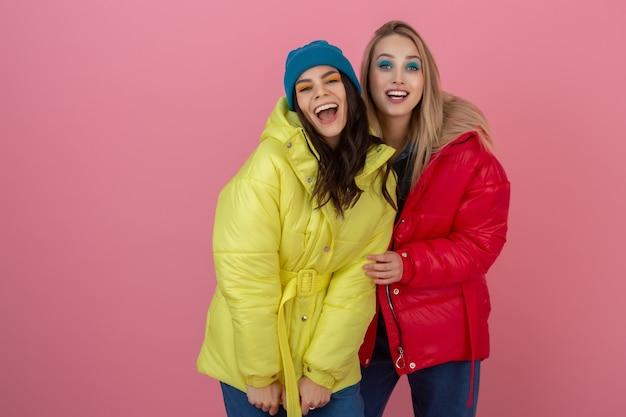 Zwei attraktive aktive frauen, die auf rosa wand in der bunten winter daunenjacke der leuchtend roten und gelben farbe aufwerfen, freunde, die spaß zusammen haben, warmer mantelmodetrend, verrückte lustige gesichter