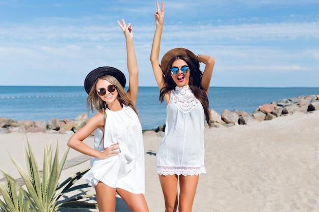 Zwei attraktive brünette und blonde mädchen mit langen haaren sitzen am strand in der nähe des meeres. sie halten die hände oben, posieren und lächeln in die kamera.