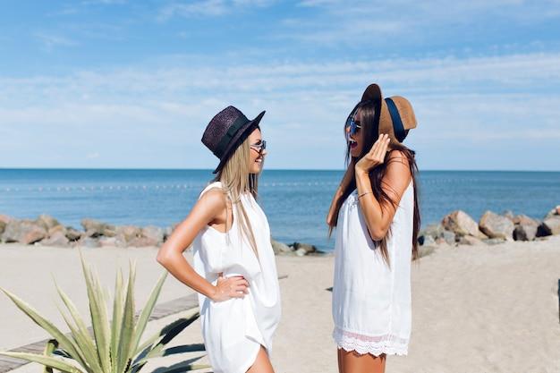 Zwei attraktive brünette und blonde mädchen mit langen haaren stehen am strand in der nähe des meeres. sie reden miteinander.