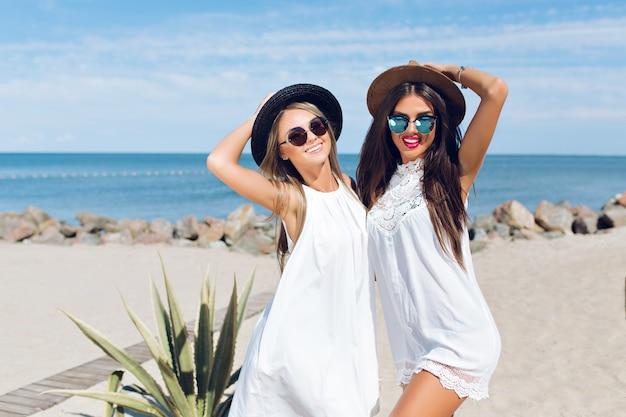 Zwei attraktive brünette und blonde mädchen mit langen haaren stehen am strand in der nähe des meeres. sie umarmen sich und lächeln in die kamera.