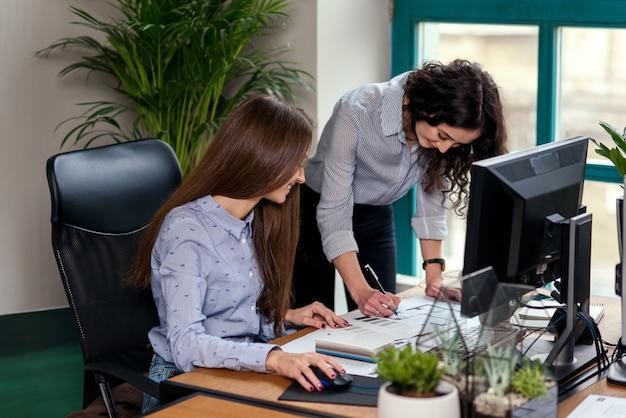 Zwei attraktive designerinnen in blauen hemden arbeiten zusammen mit neuem projekt auf pc im modernen büro.