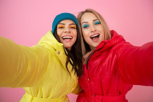 Zwei attraktive frauen, die auf rosa hintergrund in der bunten winter-daunenjacke der leuchtend roten und gelben farbe aufwerfen, freunde, die spaß zusammen haben, warmer kleidermodetrend, selfie nehmend