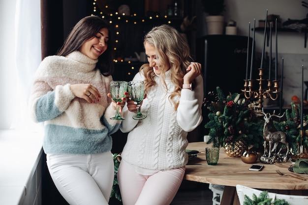 Zwei attraktive frauen in pullovern rösten gläser mit getränken am küchentisch mit weihnachtsschmuck.