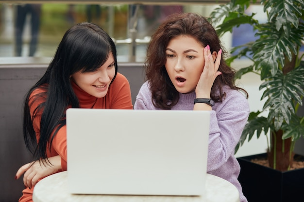 Zwei attraktive frauen mit weißem laptop, die am kaffee sitzen und auf notizbuchbildschirm mit erstaunten gesichtsausdrücken schauen, sehen etwas interessantes, während sie sich im café ausruhen.