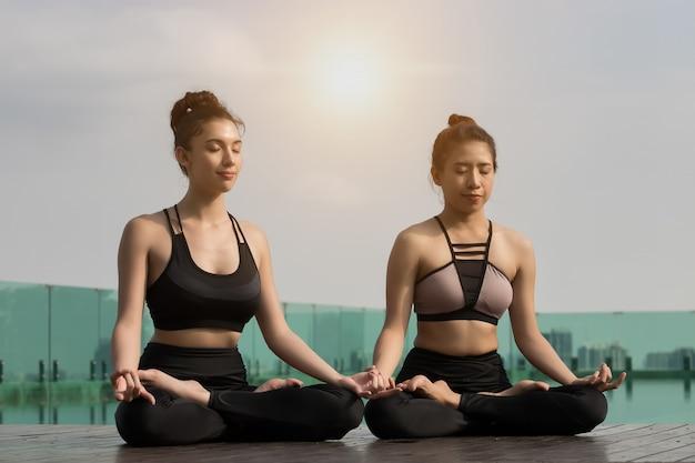 Zwei attraktive frauen spielen yoga. am pool für ihre gesundheit
