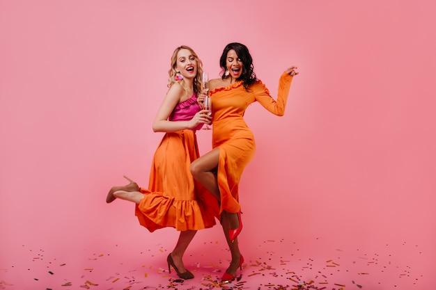 Zwei attraktive frauen tanzen auf der party