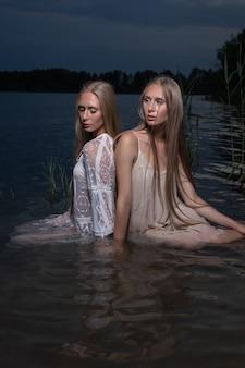 Zwei attraktive junge blonde zwillingsschwestern, die in der sommernacht in hellen kleidern im wasser des sees aufwerfen.