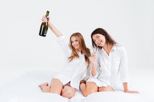 Zwei attraktive junge frauen, die eine party mit einer flasche champagner im bett haben