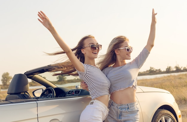 Zwei attraktive junge frauen in der nähe eines cabrio