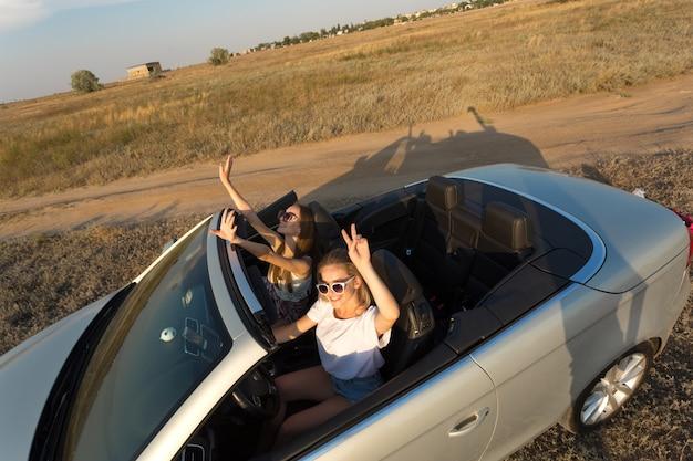 Zwei attraktive junge frauen in einem cabriolet-auto