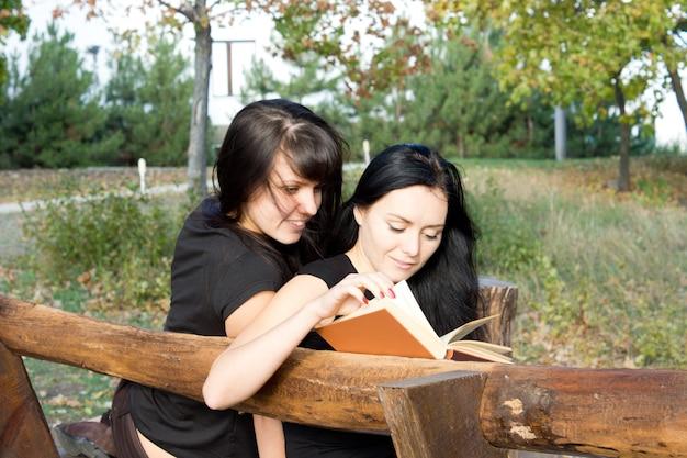 Zwei attraktive junge mädchen sitzen auf einer rustikalen holzbank und lesen zusammen ein buch