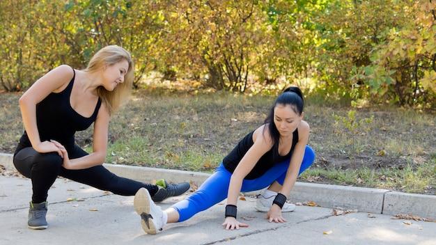Zwei attraktive junge sportlerinnen trainieren im freien und machen dehnübungen, während sie im park trainieren