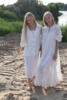 Zwei attraktive junge zwillingsschwestern, die am sandstrand in eleganten weißen kleidern aufwerfen
