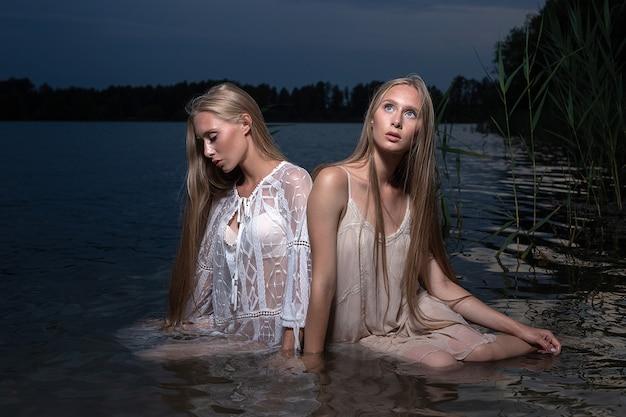Zwei attraktive junge zwillingsschwestern mit langen blonden haaren, die in der sommernacht in hellen kleidern im wasser des sees aufwerfen