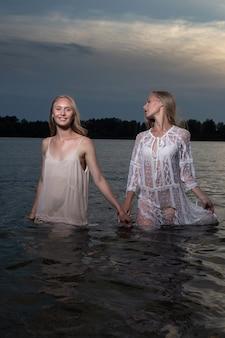 Zwei attraktive junge zwillingsschwestern mit langen blonden haaren, die in der sommernacht in hellen kleidern im wasser des sees aufwerfen.