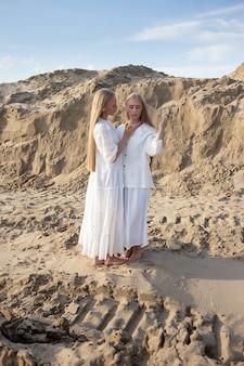 Zwei attraktive junge zwillingsschwestern posieren im sandsteinbruch in eleganter weißer kleidung