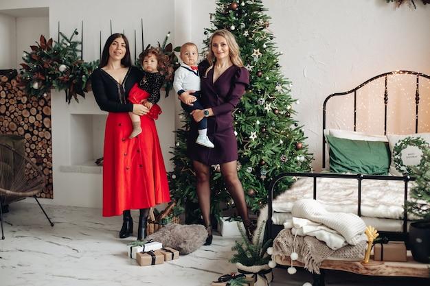 Zwei attraktive kaukasische frauen mit ihren hübschen kindern nahe dem weihnachtsbaum zu hause
