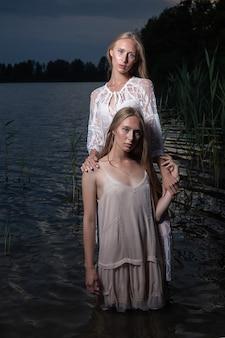 Zwei attraktive kaukasische zwillingsschwestern mit langen blonden haaren, die in hellen kleidern im wasser des sees in der sommernacht aufwerfen