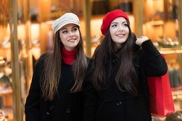 Zwei attraktive lächelnde junge frauen kaufen in der stadt