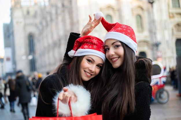 Zwei attraktive lächelnde junge frauen kaufen in mailand ein