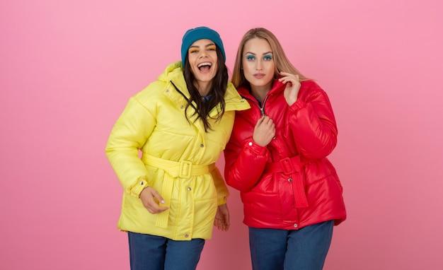 Zwei attraktive mädchen, die auf rosa hintergrund in der bunten winter-daunenjacke der leuchtend roten und gelben farbe aufwerfen