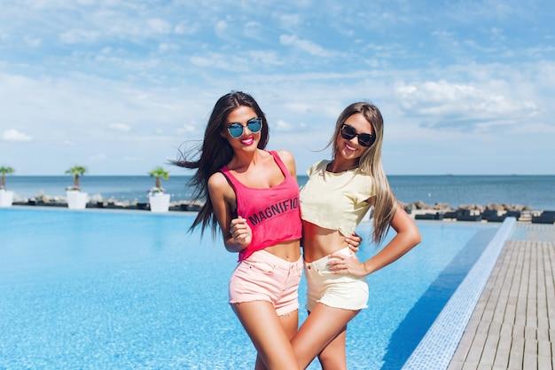 Zwei attraktive mädchen mit langen haaren posieren in der nähe des pools auf der sonne. sie lächeln in die kamera.