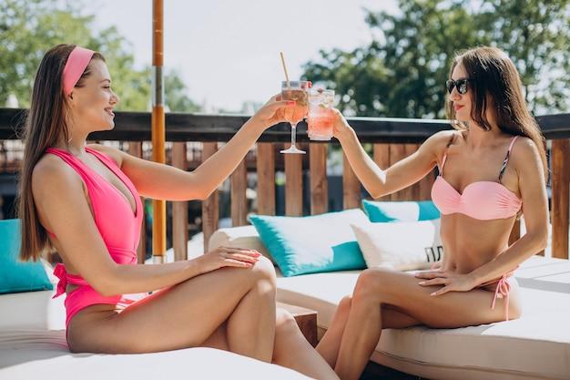 Zwei attraktive mädchen trinken cocktails am pool