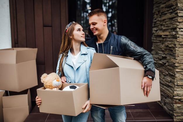 Zwei attraktive personen mit kisten auf den händen, die in ein neues haus umziehen.