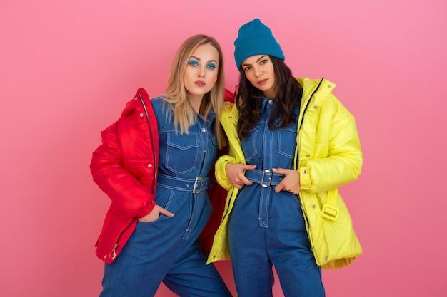 Zwei attraktive stilvolle frauen, die auf rosa hintergrund in der bunten winter daunenjacke der roten und gelben farbe, warmer kleidungsmodetrend aufwerfen