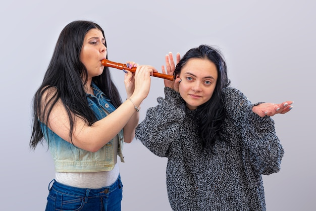 Zwei attraktive teenager-mädchen, die spaß mit hölzerner flöte lokalisiert auf hellem hintergrund haben
