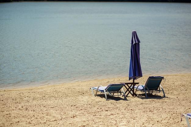 Zwei aufenthaltsräume mit sonnenschirm am strand