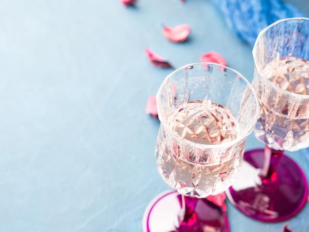 Zwei aufgehaltene champagnergläser auf blau texturedwith rosafarbenen getrockneten blumen. valentinstag, der romantische datumseinladung wedding ist
