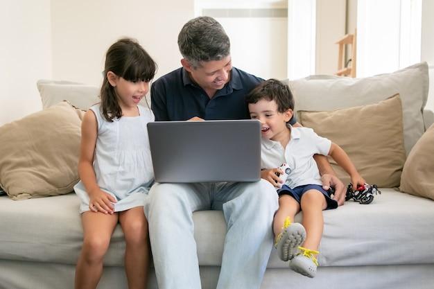 Zwei aufgeregte glückliche kinder, die inhalt auf laptop mit ihrem vater ansehen, während sie zu hause auf der couch sitzen
