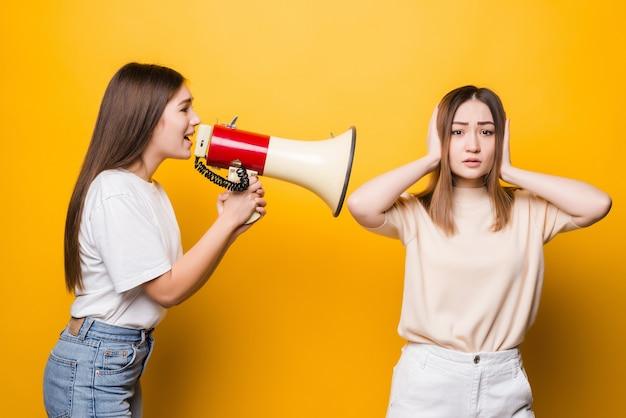 Zwei aufgeregte junge freundinnen in den lässigen t-shirt-denim-kleidern, die lokal auf gelber wand aufwerfen. menschen lifestyle-konzept. kopieren sie den speicherplatz. schreien sie im megaphon und spreizen sie die hände
