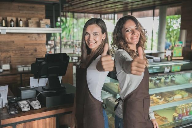 Zwei aufgeregte kellnerin, die daumen oben in einem café zeigt