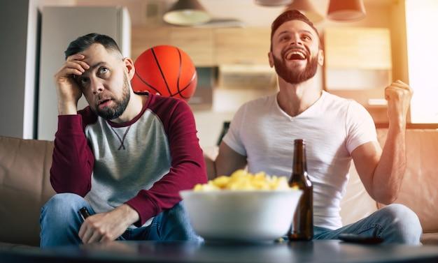 Zwei aufgeregte lustige junge freunde, die basketballfans sehen, die fernsehen und schreien, während sie sich auf der couch ausruhen