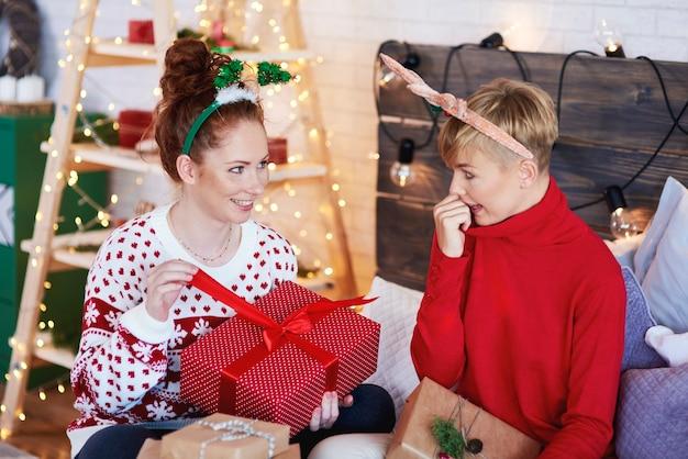 Zwei aufgeregte mädchen, die weihnachtsgeschenk öffnen