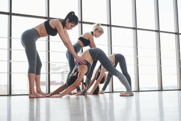 Zwei ausbilder, die mädchen fitness-posen unterrichten, in der weißen großen turnhalle