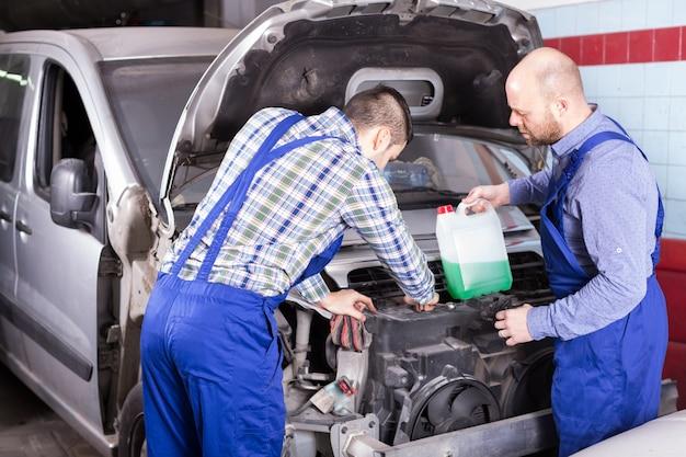 Zwei automechaniker an der werkstatt