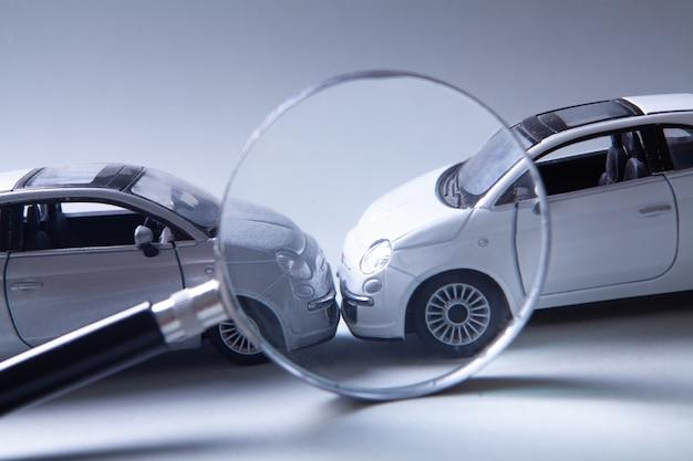 Zwei autos kollidierten, versicherung. maschinen und lupe auf dem tisch