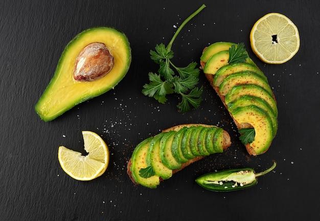 Zwei avocado-sandwiches auf dunklem roggenbrot aus frisch geschnittenen avocados auf einem schwarzen steintisch